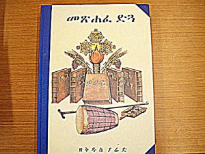 Figure 3. The front cover of Metshafe Digua Zeqidus Yared (Book of Digua). The cover shows the five volumes of Yared's Zema composition: Digua, Tsome Digua, Miraf, Zimare, and Mewasit. Processional Ethiopian cross, drum, sistrum, and tau-cross staff are also illustrated in the cover.
